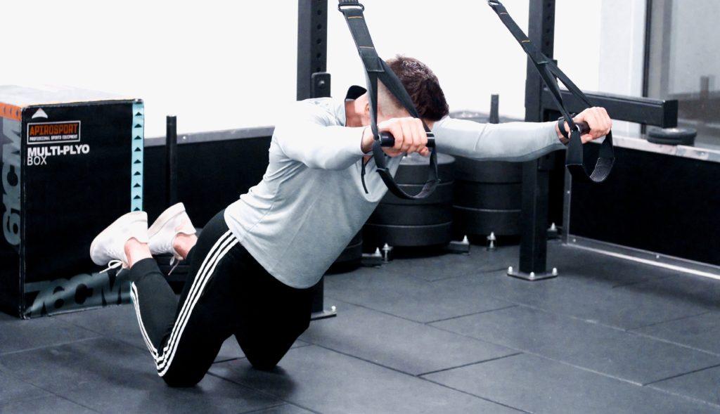 Ćwiczenie angażujące mięsień prosty brzucha oraz core przy użyciu TRX na strefie funkcjonalnej w warszawskiej siłowni Cityfit w Sadyba Best Mall