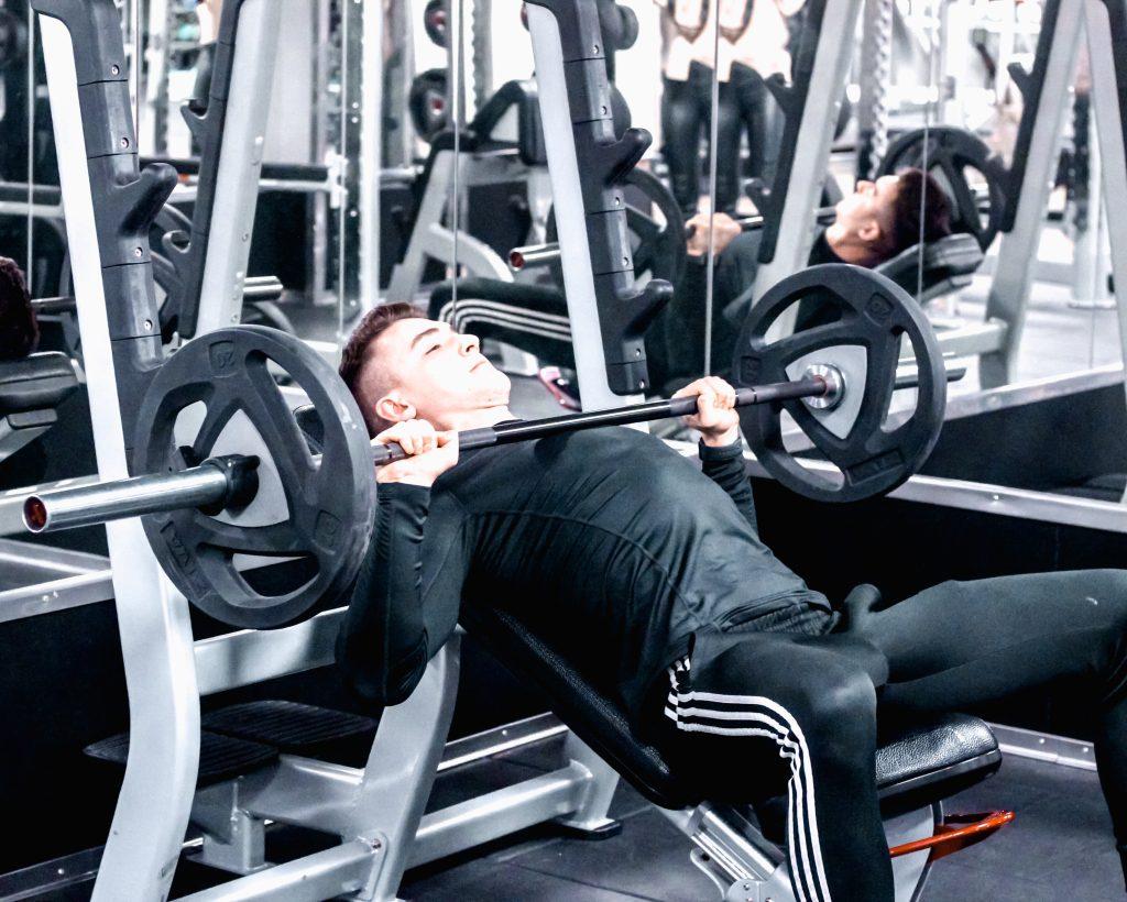 wyciskanie sztangi na skosie dodatnim w trakcie personalnego treningu kulturystycznego na jednym z warszawskich fitness klubów - czy warto ćwiczyć z trenerem personalnym?