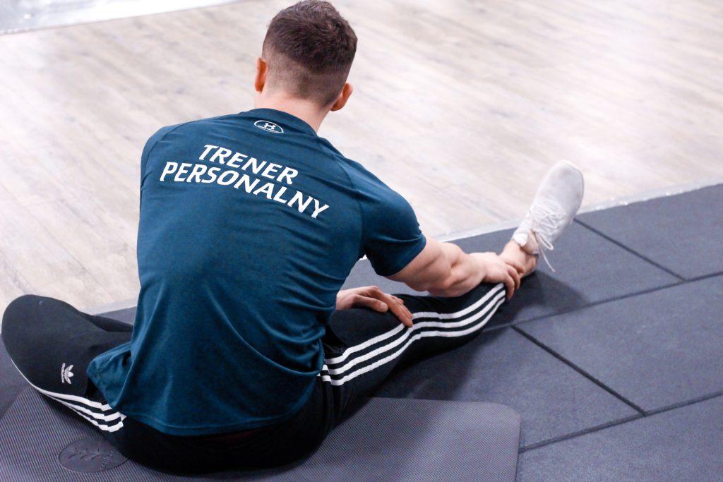 trener personalny demonstruje prawidłowe rozciąganie dwugłowych uda oraz mięśni grzbietu na strefie funkcjonalnej cityfit sadyba