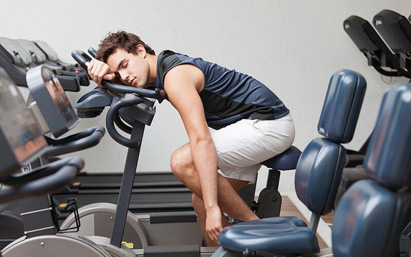 mężczyzna śpiący na siłowni z przemęczenia - dłuższa przerwa w treningach
